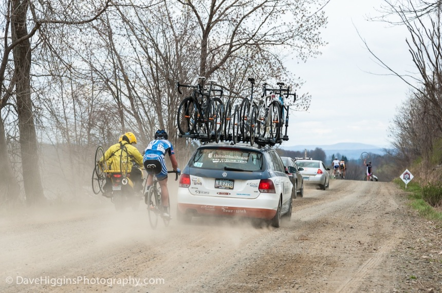 One rider drafts a team car while another signals for a replacement wheel